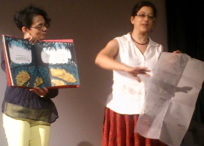 Karthika Nair and Anita Roy hold up the book and the first drafts of the illustrations during the presentation.